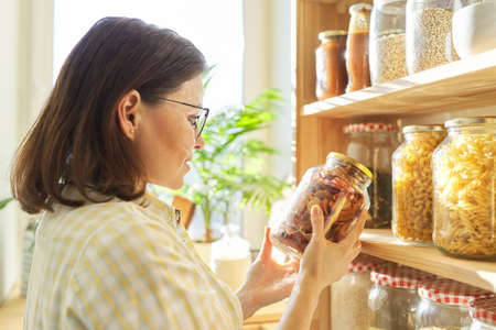 Food storage in pantry, woman holding jar of dry sun-dried apples in hand. Pantry interior, wooden shelf with food cans and kitchen utensils