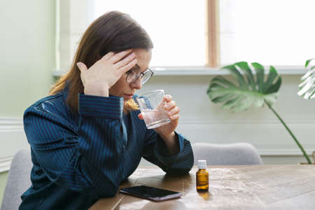 Nervous disorder, depression, nervousness, age-related health problems. Mature woman dripping drops with glass of water, drinking sedative medicine, at home in pajamas, copy space