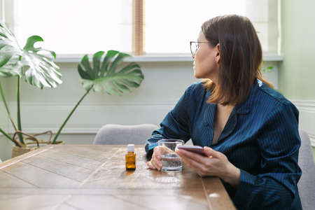 Excited sad mature woman reading smartphone. Female in pajamas sitting at home, drinking water with sedative drops. Physical and psychological mental health of middle-aged people, copy space