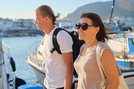 Middle-aged man and woman walking together holding hands. Love, romance, communication mature people
