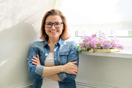 Beautiful mature woman at home with flowers, smiling female standing near window with bouquet of lilacs, copy space