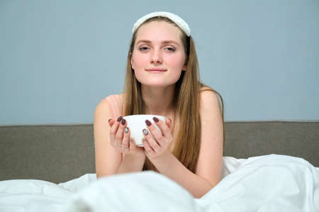 Beautiful young woman 20 years old blonde in bed with cup of tea, morning, white bed, background gray wall