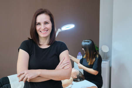 Portrait of confident female specialist in spa beauty salon, female cosmetologist looking at camera with crossed arms