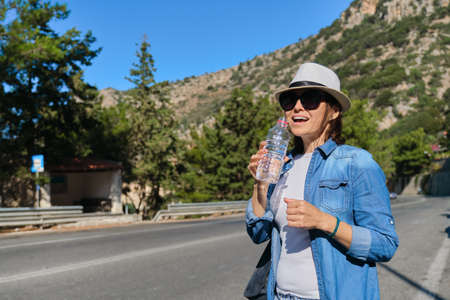 Beautiful mature woman standing on mountain road drinking water from bottle on hot sunny day. Acting healthy lifestyle and healthy eating, copy space