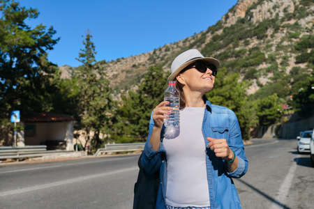 Beautiful adult female tourist removing thirst, drinking water from plastic bottle, traveling on mountain road on hot sunny day, copy space