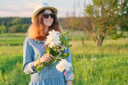 Portrait of young smiling beautiful girl in sunglasses hat with bouquet of wildflowers, sunset in meadow, copy space, rural scenery, golden hour