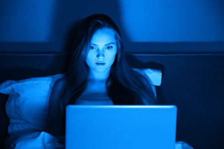 Young woman sitting at home in bed at night with laptop, girl watches movie, communicates on social networks, reads and watches news