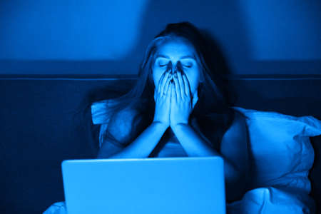 Young woman sitting at home in bed at night with laptop. Girl holds head in her hands, emotional stress, bad news, depression, headache Banque d'images