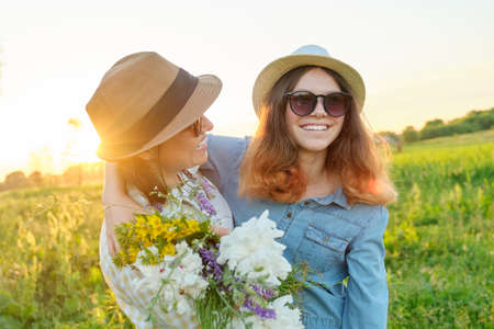 Mothers day, hugging happy smiling teenager daughter with mother in meadow with bouquet of spring flowers