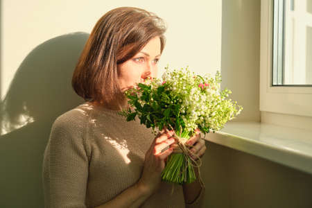 Close up portrait of mature woman with bouquet of flowers. Female at home near sunny window