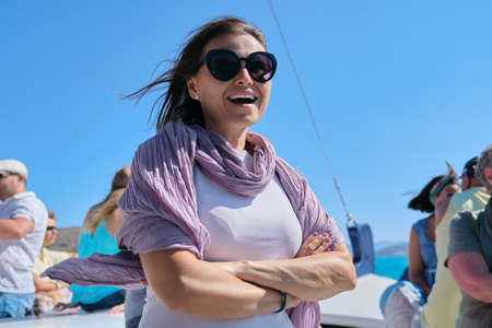 Boat trip on small ship on bay. Mature female with group of tourists enjoying sea voyage, sunny summer day, picturesque landscapes on horizon