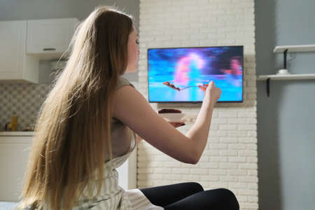 Young woman sitting at home watching tv and eating. Banque d'images