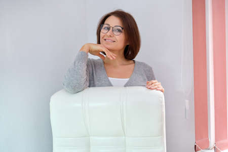 Mature beautiful business woman with glasses, cashmere sweater near office leather white armchair, copy space