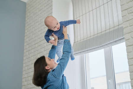 Happy young beautiful mother playing with toddler son, woman raising baby up, flying and laughing boy. Family is happy at home, near window, copy space