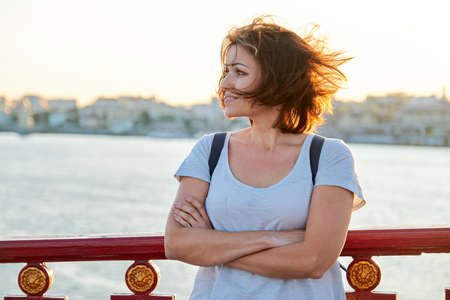 Outdoor portrait of mature beautiful happy woman with arms crossed, female walking with backpack on bridge on summer day, golden hour. Woman looks away, copy space Banque d'images