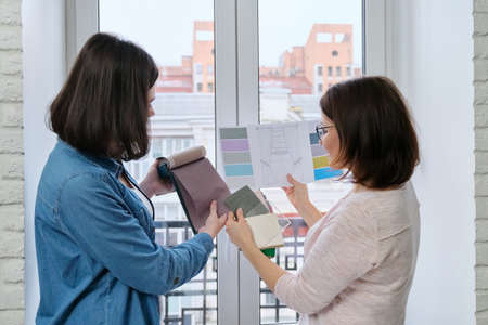 Female designer and client working with fabric samples. Selecting fabrics and design of curtains, females near window with sketch and materials