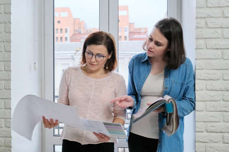 Two women designer and customer working choosing fabrics for curtains, furniture upholstery. Looking different models of curtains, colors on sketches