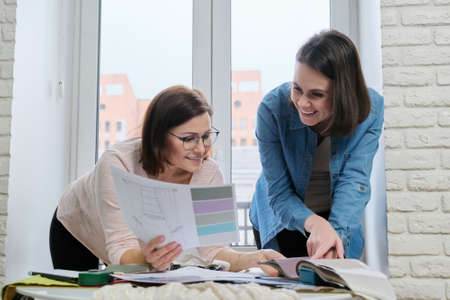 Two women designers working with fabric samples for interior. Choosing fabrics for curtains, furniture upholstery, calculating cost