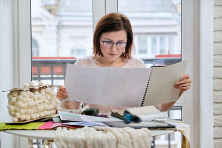 Woman interior designer working at table in office with samples of interior decorative fabrics for curtains, upholstery, accessories. Decorator choosing fabrics, sketching and calculating