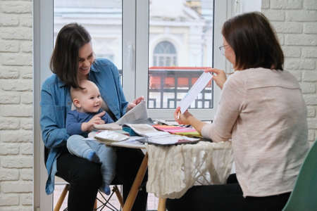 Woman textile designer and young mother with baby choosing fabrics for curtains, pillows, bedspreads, upholstery. Women look at fabric patterns and curtains Zdjęcie Seryjne