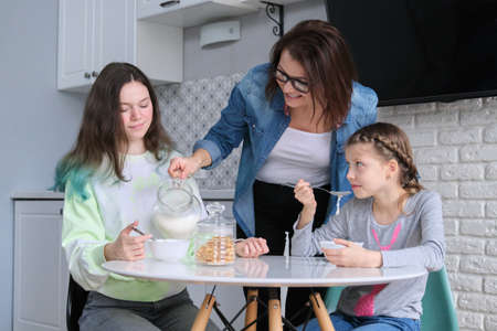 Children with mother eating at home in kitchen, two girls sitting at table with plates of corn flakes and milk. Family, eating, communication, health concept. Banque d'images