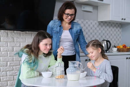 Happy mother caring for daughters in kitchen. Eating girls sitting at table, morning breakfast, milk in jug and sweet corn flakes. Family, eating, communication, health concept Banque d'images
