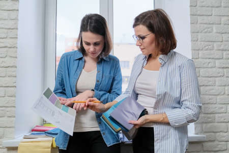 Two women interior designer and client choosing fabrics for home textile decoration, curtains, furniture upholstery