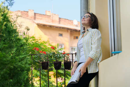 Beautiful mature woman in home clothes on open balcony reading magazine, copy space. Home balcony decorated with green plants and flowers Banque d'images