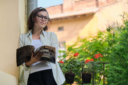 Mature woman standing on open balcony in isolation, female reading magazine alone, quarantined during viral infection, copy space
