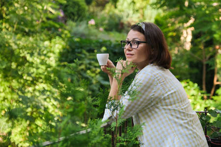 Beautiful mature woman in home clothes on open balcony with cup of coffee, smiling female looks away, in profile, copy space. Home balcony decorated with green plants and flowers