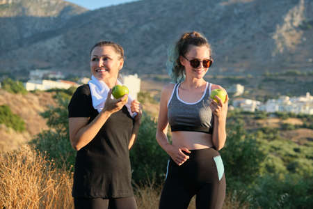 Family mother and daughter teenager in sportswear eating apples after exercise, jogging in nature, sunny day in mountains. Active healthy lifestyle and food, natural vitamins, diet products