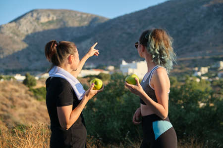 Family mother and daughter teenager in sportswear eating apples after exercise, jogging in nature, sunny day in mountains. Active healthy lifestyle and food, natural vitamins, diet products Foto de archivo