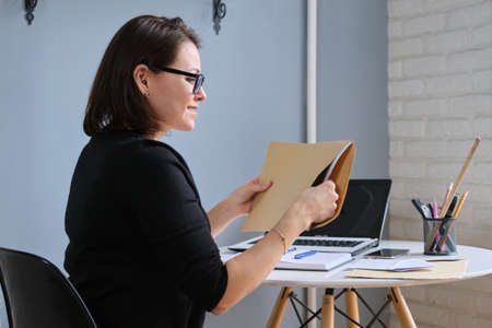 Mature woman sitting at home at desk with laptop, received an envelope with letter, smiling female taking out paper document Banque d'images