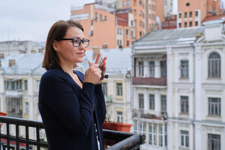 Portrait of mature woman with cup of tea standing on outdoor balcony. Female looking at city street, urban background, copy space