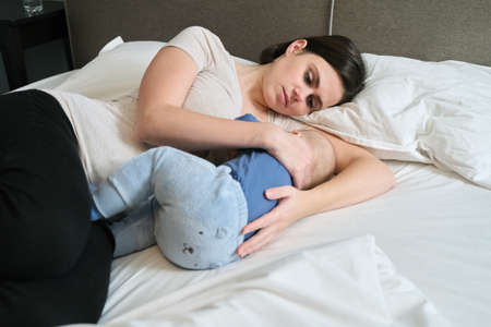 Young mother breast feeding her son, mom nursing hugging baby, mother and toddler lie together at home on bed, baby eating and falling asleep