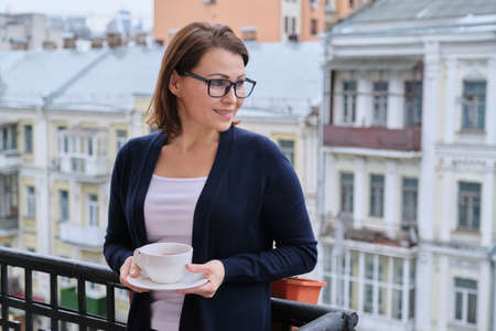 Mature woman standing on open balcony with cup of tea, female looks at city while in isolation, quarantined during viral infection, copy space