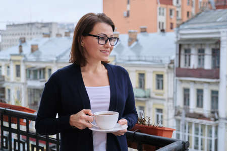 Portrait of mature woman in glasses, cardigan with cup of tea on open balcony in city. Background urban architecture, buildings, smiling female looks away, copy space Banque d'images