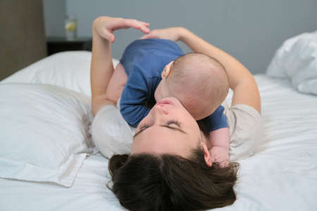 Young mother playing with toddler son, smiling woman holding baby in arms, parent and baby together at home lying in bed, view from above