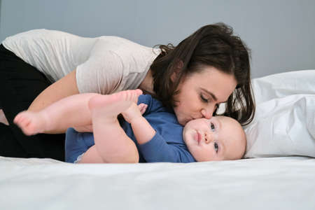 Young mother lovingly kisses her son toddler. Woman playing with baby while lying in bed
