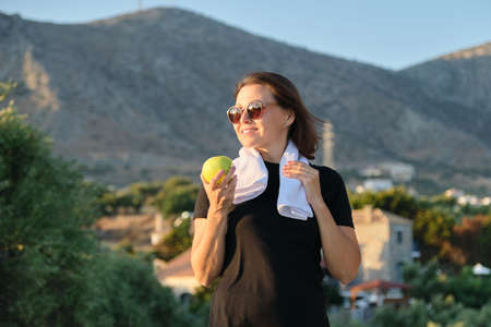 Smiling mature woman eating green apple. Female after fitness in mountains, diet healthy food, natural vitamins