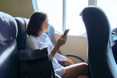 Passenger of sea ferry mature woman traveling in cabin of boat. Female sitting on armchair resting, using smartphone. Sea transport, travel, tourism