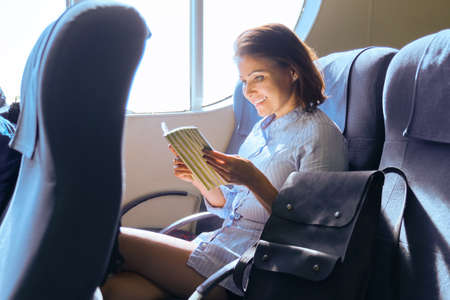 Adult female passenger sitting on armchair near window in ferry cabin. Female taking sea voyage reading magazine, book. Sea transport, travel, tourism