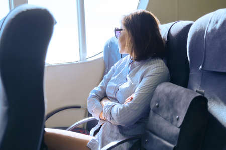 Passenger shipping, woman sitting inside comfortable sea ferry, resting, looking out the window, sea trips, tourism