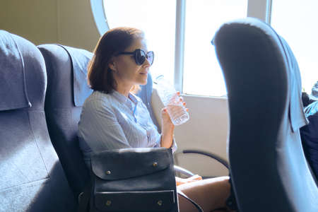 Passenger shipping, woman sitting inside comfortable sea ferry, resting, drinking water from bottle, sea trips, tourism