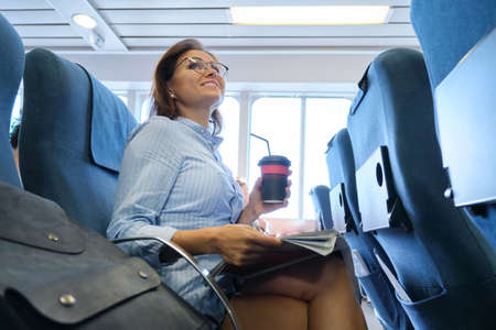 Passenger shipping, woman sitting in cabin of comfortable sea ferry, resting reading magazine drinking coffee, sea trips, tourism