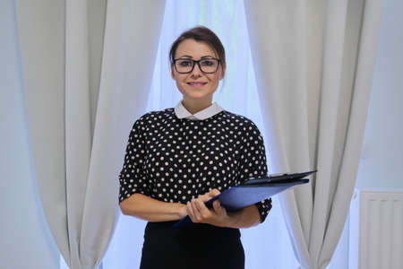 Successful business mature woman with documents, female working in hotel, real estate, posing looking at camera Banque d'images