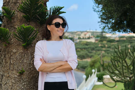 Beautiful middle-aged woman with arms crossed, female in sunglasses near tropical tree, copy space. Successful female resting at resort