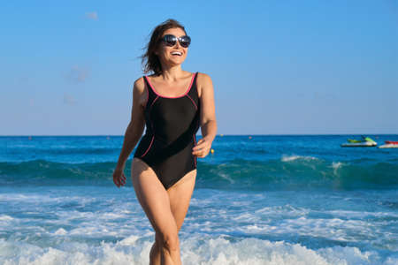 Mature smiling woman in swimsuit with sunglasses walking along beach. Beauty, health, body, relaxation for middle-aged people. Blue sky, sea with waves background, copy space