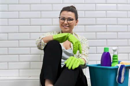 Portrait of smiling woman in gloves sitting on floor in bathroom with bucket of detergent. Happy female after cleaning house