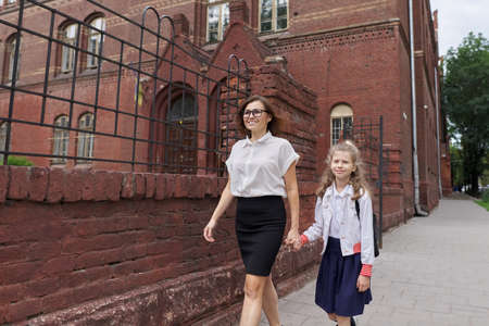 Elementary school schoolgirl walking with mom holding hands, talking parent and child on the way to school. Start of study, back to school